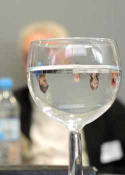 ein Weinglas mit Wasser in dem sich Gesichter spiegeln